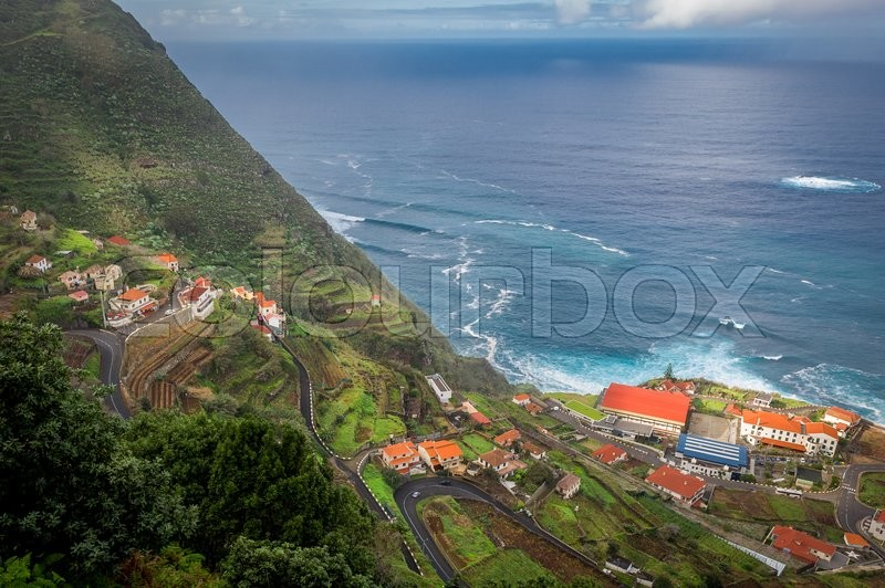 Stock image of 'Aerial view of steep serpentine road from the mountains down to Porto Moniz town on the shore of Atlantic ocean. Madeira island, Portugal.'