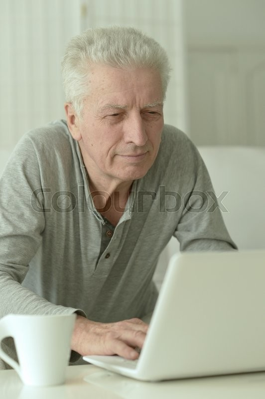 Stock image of 'Portrait of  senior man  in the kitchen at home with laptop'