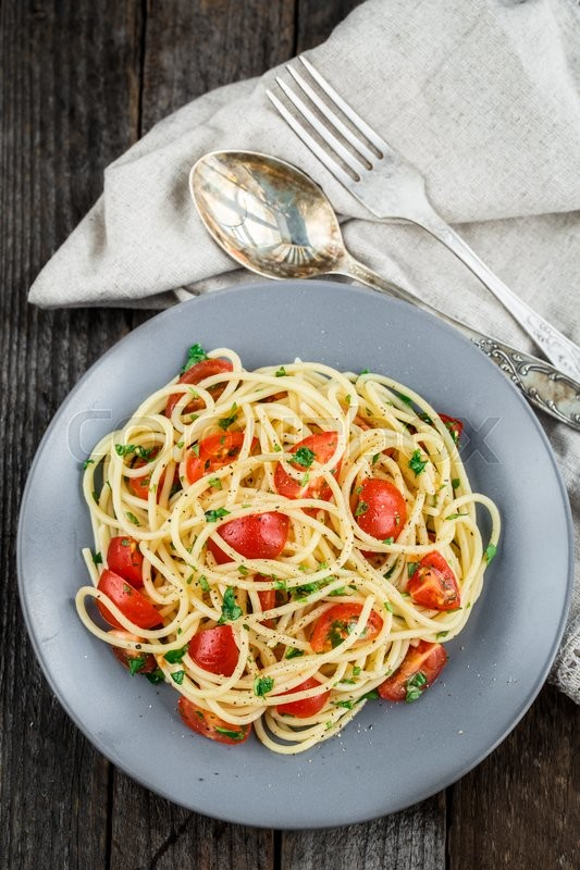Stock image of 'Spaghetti pasta with cherry tomatoes and parsley on rustric background'
