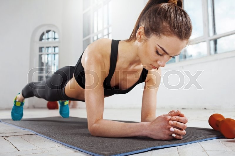Stock image of 'Beautiful young slim woman  doing push ups at the gym with orange dumbbells'