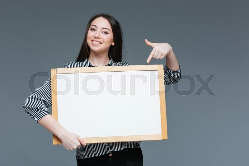 Stock image of 'Smiling businesswoman pointing finger on blank board over gray background'