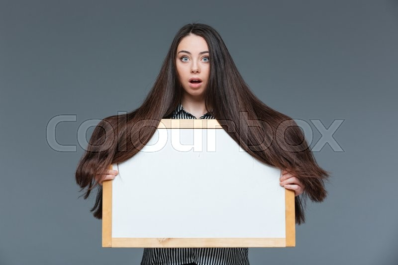Stock image of 'Beautiful woman with long hair holding blank board over gray background'