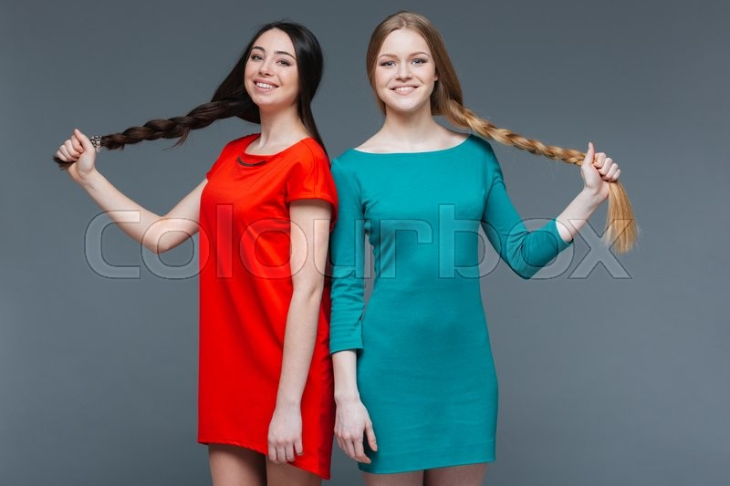 Stock image of 'Two smiling beautiful women standing and showing their long braids over grey background'
