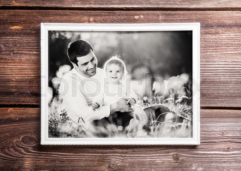 Stock image of 'Fathers day composition. Photo of father and son in white picture frame. Studio shot on wooden background.'