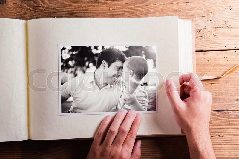 Stock image of 'Fathers day composition. Hands of unrecognizable man holding a photo album, black-and-white pictures. Studio shot on wooden background.'