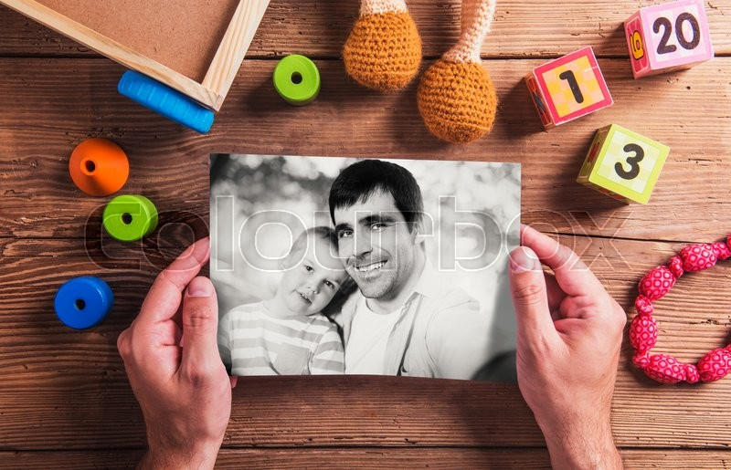 Stock image of 'Fathers day composition. Unrecognizable man holding black-and-white picture. Various toys. Studio shot on wooden background.'