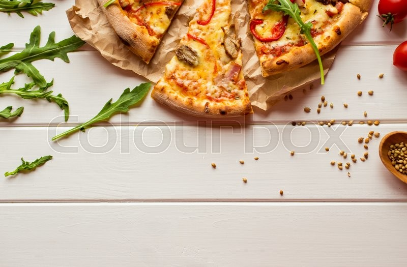 Stock image of 'Top view of fresh baked pizza with slice served on wooden table'