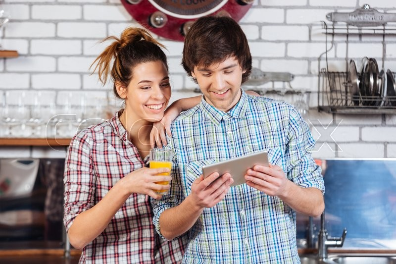 Stock image of 'Happy couple drinking orange juice and using tablet on kitchen'