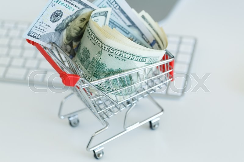 Stock image of 'Dollars in the shopping cart on a computer keyboard - concept of online shopping'