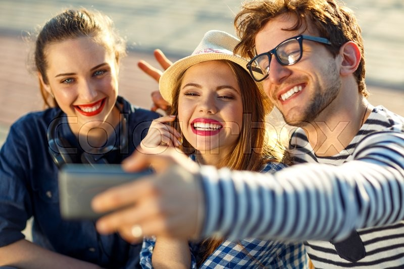 Friendship, leisure, summer, technology and people concept - smiling friends making selfie outdoors, stock photo