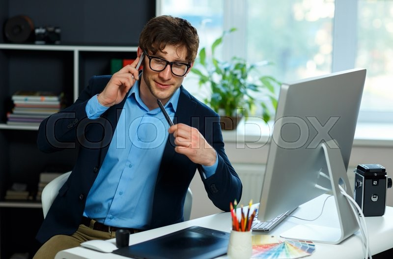 Stock image of 'Handsome young man working from home office and using smartphone - modern business concept'