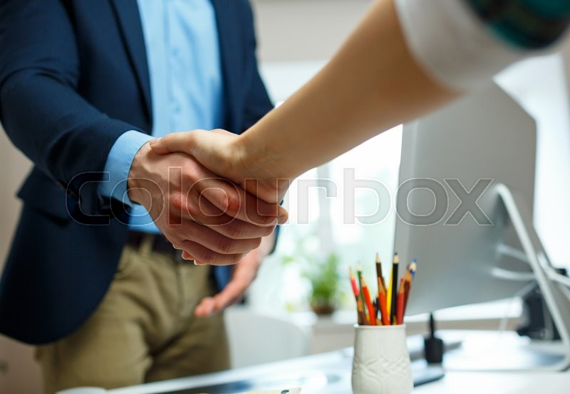 Stock image of 'Young businessman and businesswoman shaking hands in office'