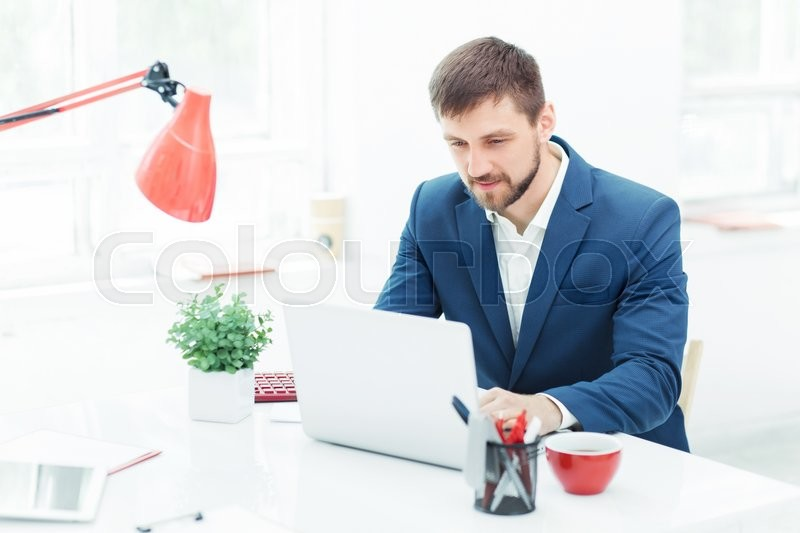 Stock image of 'Elegant successful  businessman sitting at the office and looking throw the information on his laptop'