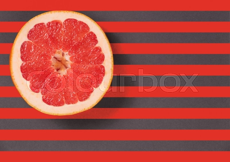 Stock image of 'Red juicy grapefruit on a striped background top view. Striped background in red and gray stripes. Red grapefruit located top left. Lines texture.  Diagonal lines.'