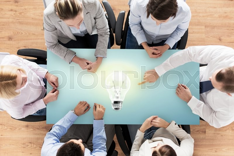 Stock image of 'business, people and team work concept - close up of creative team sitting at table and pointing finger to lighting bulb in office'