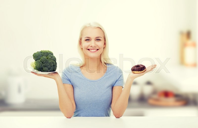 Stock image of 'healthy eating, junk food, diet and choice people concept - smiling woman choosing between broccoli and donut over kitchen background'