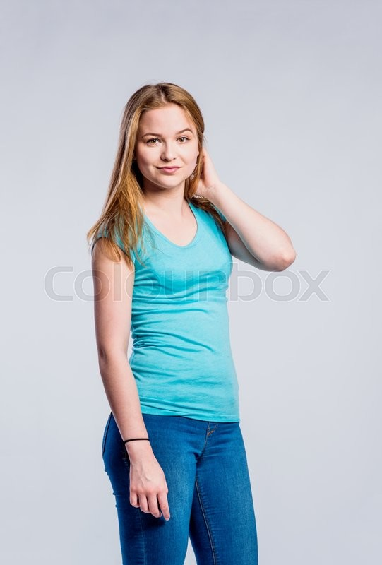 Stock image of 'Teenage girl in jeans and turquoise t-shirt, young woman, studio shot on gray background'