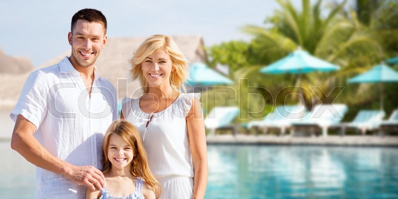 Stock image of 'summer holidays, travel, tourism, vacation and people concept - happy family over hotel resort swimming pool and sun beds background'