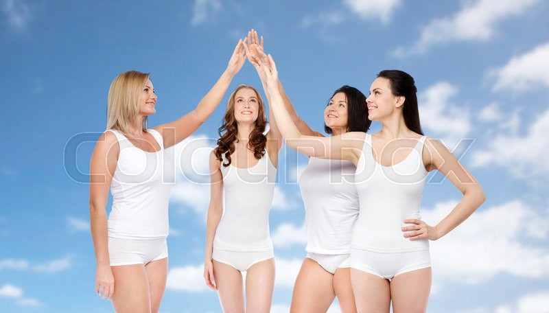 Stock image of 'gesture, friendship, beauty, body positive and people concept - group of happy different women in white underwear making high five over blue sky and clouds background'