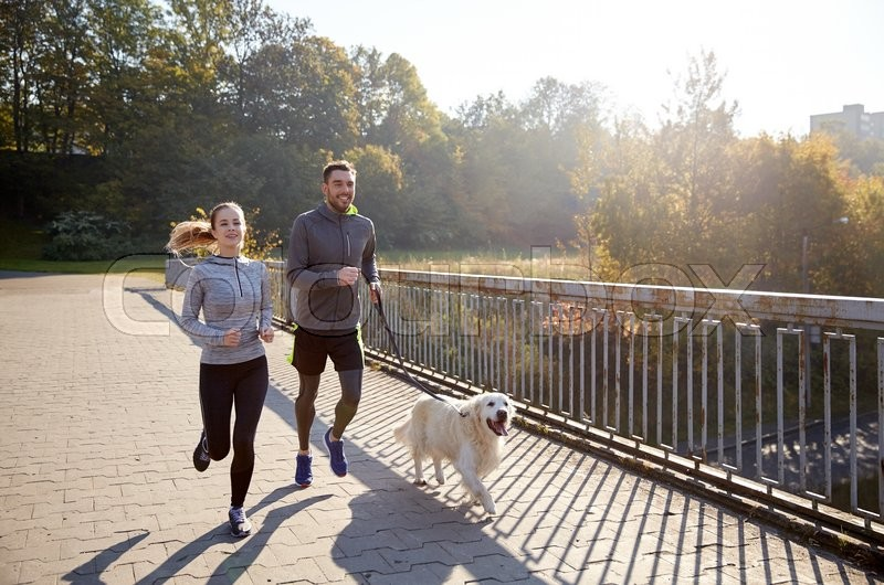 Fitness, sport, people and jogging concept - happy couple with dog running outdoors, stock photo