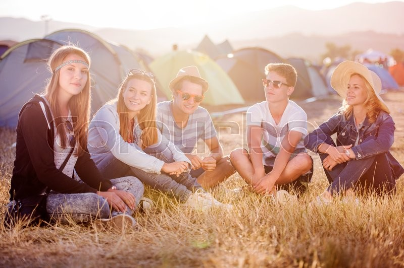 Stock image of 'Group of teenage boys and girls at summer music festival, sitting on the ground in front of tents'