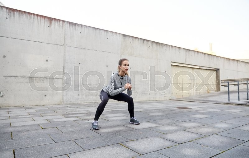 Stock image of 'fitness, sport, exercising and healthy lifestyle concept - happy woman doing squats outdoors'