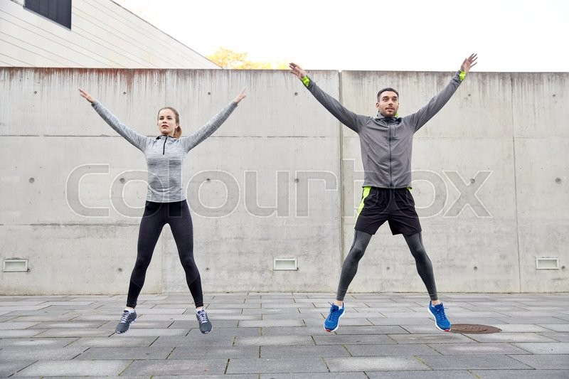 Fitness, sport, people, exercising and lifestyle concept - happy man and woman doing jumping jack or star jump exercise outdoors, stock photo
