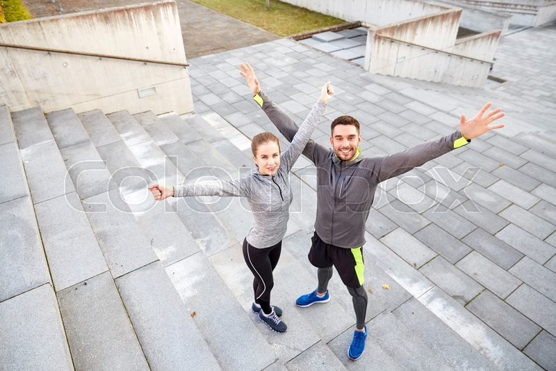 Stock image of 'fitness, sport, people and lifestyle concept - happy smiling couple outdoors on city street'