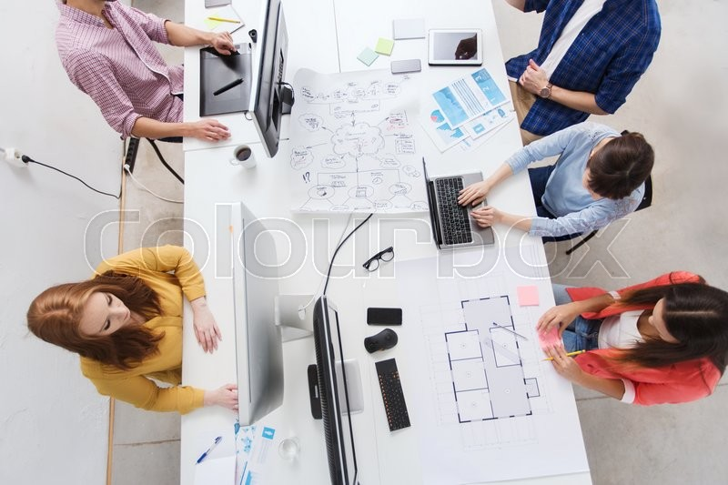 Stock image of 'business, startup and people concept - creative team with computers, blueprint and scheme at office'