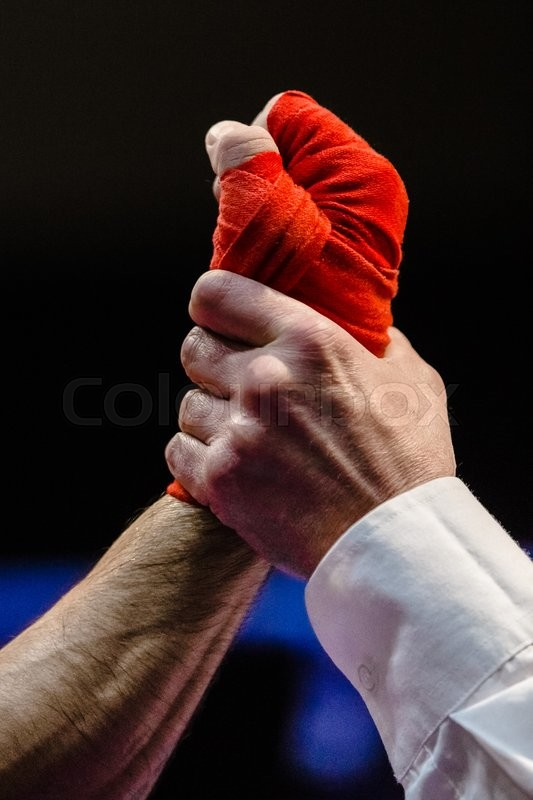 Stock image of 'closeup of referee raises hand of boxer winner after fight in Boxing'
