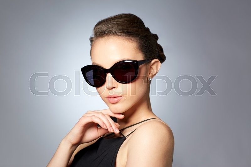 Accessories, eyewear, fashion, people and luxury concept - beautiful young woman in elegant black sunglasses over gray background, stock photo