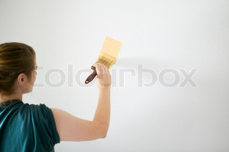 Woman painting white wall with bright yellow paint for Neon yellow wall paint