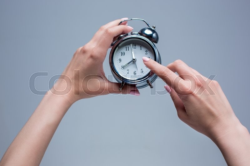 Stock image of 'The female hands and old style alarm clock on gray background'