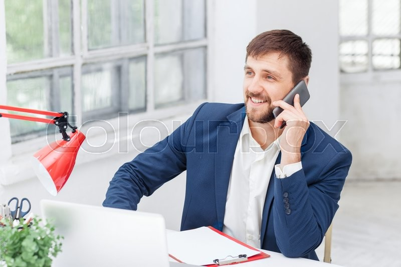 Stock image of 'Portrait of businessman talking on mobile phone in office'