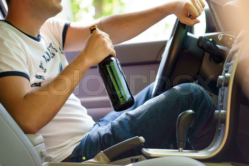 Stock image of 'Man drinking beer while driving the car.'
