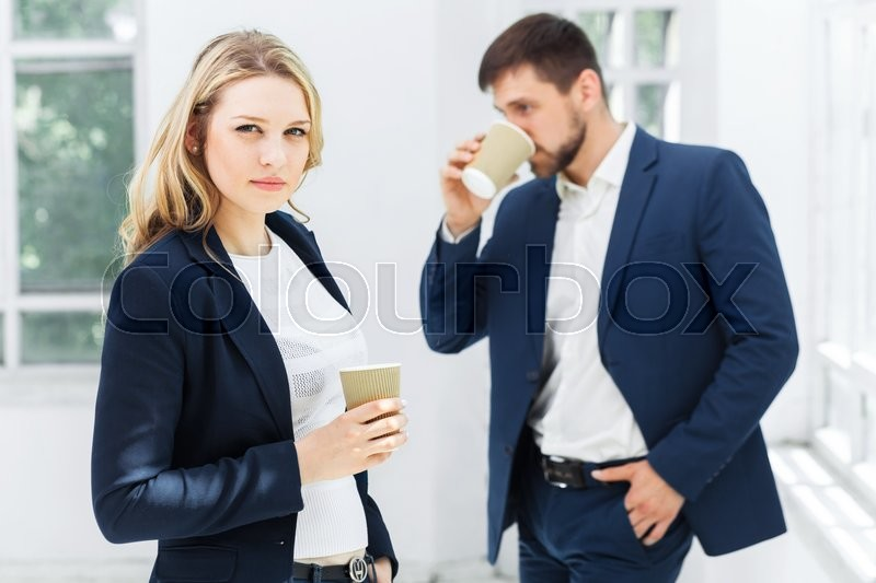 Young colleagues having coffee break, chatting in office, stock photo