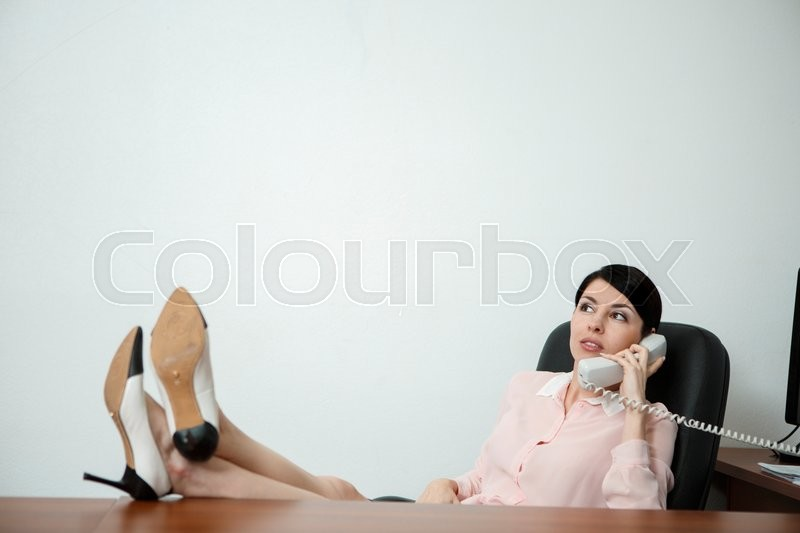 Stock image of 'Relaxed business woman sitting in a chair with legs over the table and talking over phone.'
