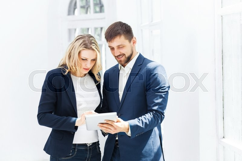 Stock image of 'The smiling male and female office workers with laptop'
