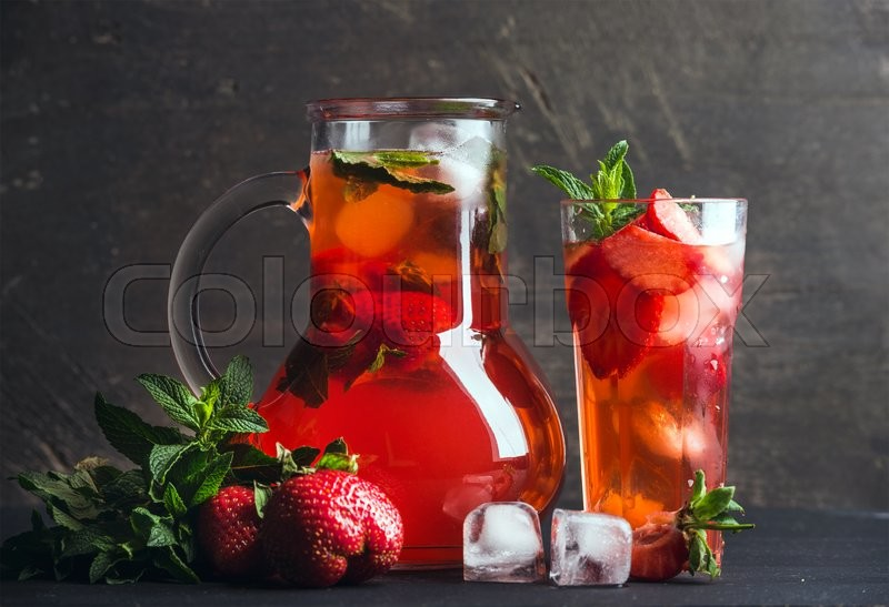 Stock image of 'Homemade red strawberry lemonade  with mint and ice cubes on dark wooden background'