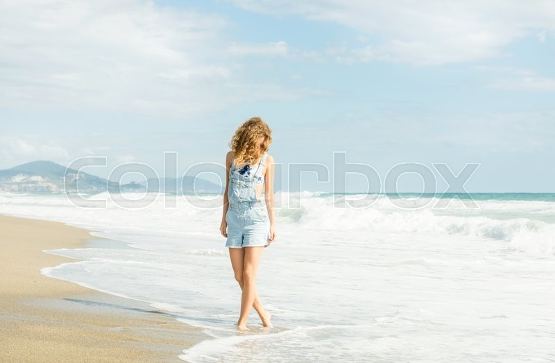 Stock image of 'Young woman in blue denim jumpsuit walking along beach and the stormy ocean on sunny day'