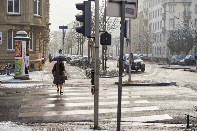 STRASBOURG, FRANCE - JAN 20, 2016: Silhouette of woman crossing street with umbrella on a snowy day, stock photo