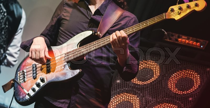 Rock music concert, bass guitar player on a stage, selective focus, stock photo