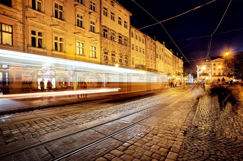 Stock image of 'Street with tramway rails and tracks from headlights at night'