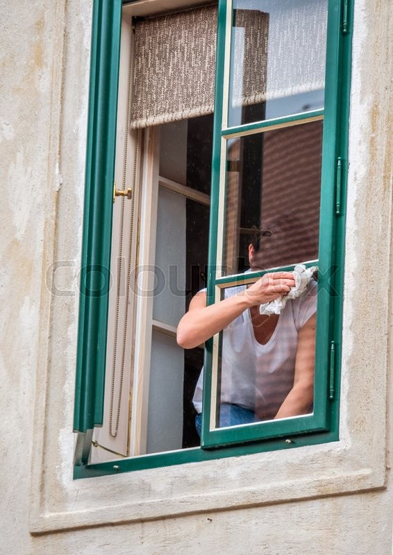 Stock image of 'woman brushing the window'