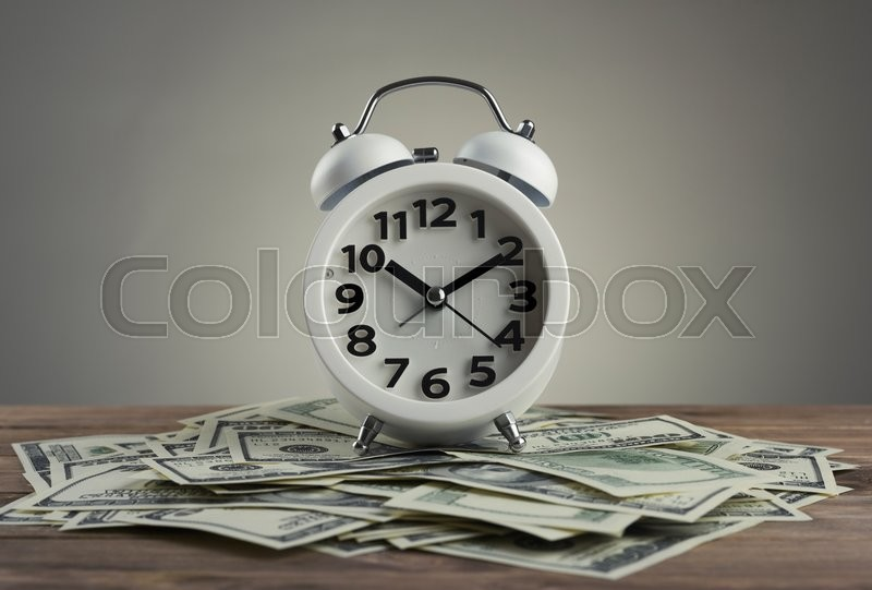 Stock image of 'Time is money concept with clock and dollars'