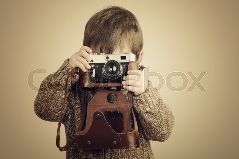 Stock image of 'little boy taking pictures with old retro camera'