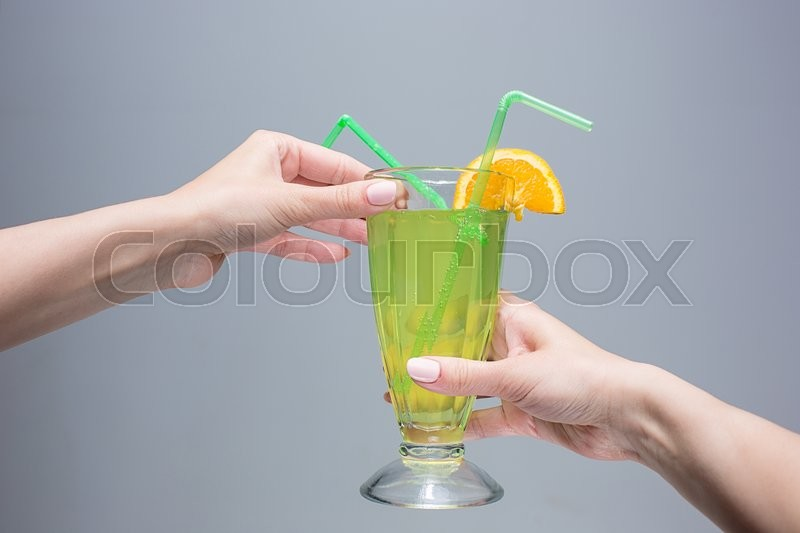 Stock image of 'The female hands with cocktail on a gray background'