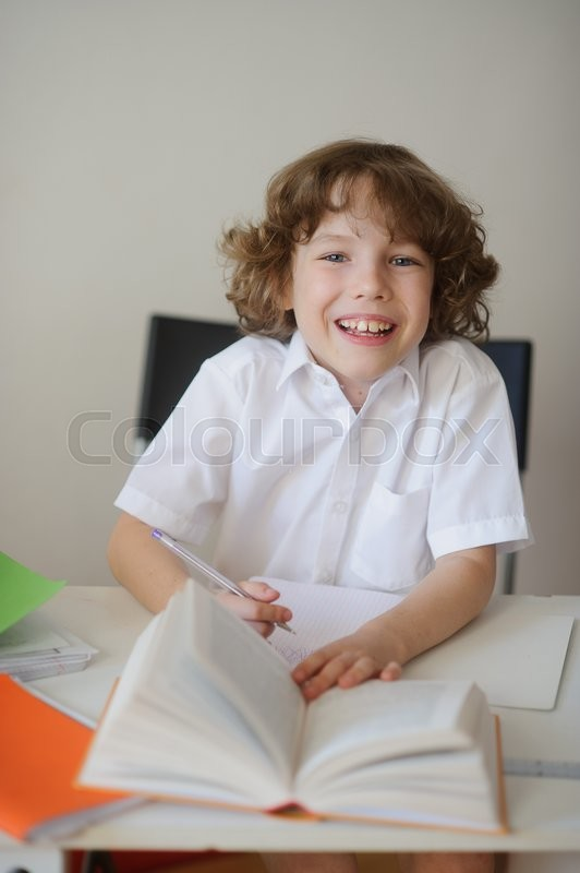Stock image of 'The curly-haired boy in a white shirt sitting at her desk. On the table, books and notebooks.  Child laughs'