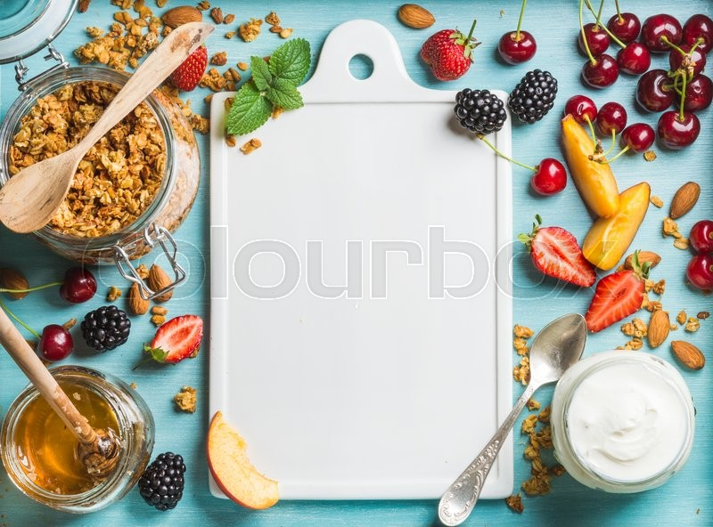 Healthy breakfast ingredients. Oat granola in open glass jar, yogurt, fruit, berries, honey and mint on blue background with white ceramic board in center, top view, copy space, stock photo