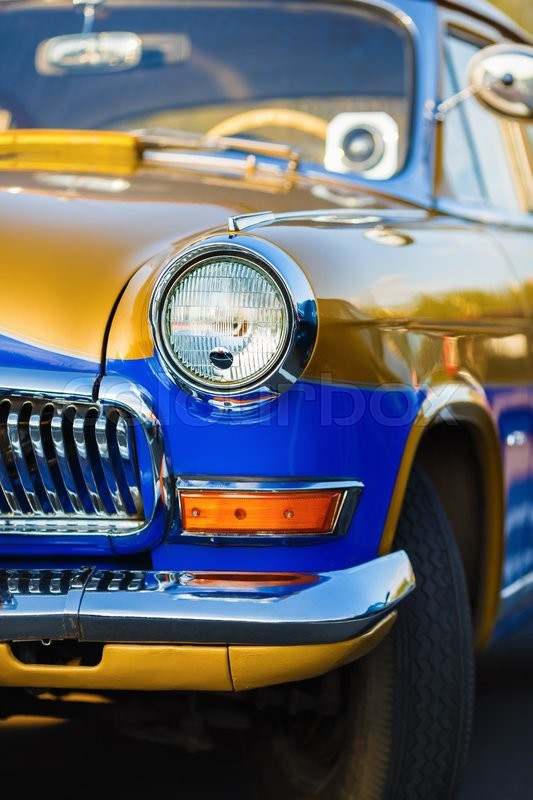 Stock image of 'Vintage retro car. Close-up of retro car. Old vintage car. Vertical shot. Selective focus on the car's headlight.'